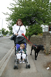 Mother with her baby son in his buggy out walking the pet dog,
