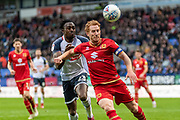 Captain Dean Lewington of MK Dons shields the ball from the attacking Joe Dodoo of Bolton Wanderers during the EFL Sky Bet League 1 match between Bolton Wanderers and Milton Keynes Dons at the University of  Bolton Stadium, Bolton, England on 16 November 2019.