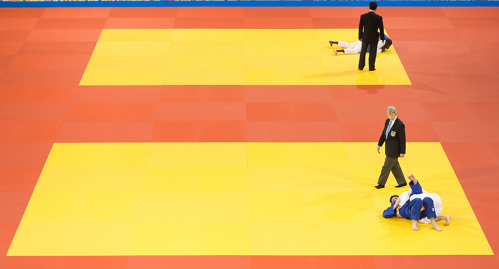 Officials look on as contestants take part in the 1/4 finals in judo at the 2015 Pan American Games in Toronto, Canada, July 13,  2015.  AFP PHOTO/GEOFF ROBINS