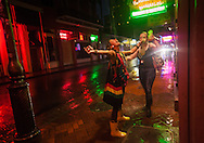 New Orleans, Louisiana, August 28th, 2012, Women drinking hurricanes in the rain on Bourbon Street as Hurricane Isaac makes landfall as a category hurricane.