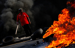 An anti-government protester is seen amid smoke and fire of burning tires as they prepare to face-off Thai army during pitched battles on the streets of Bangkok, Thailand, 13 April 2009. Thai Prime Minister Abhisit Vejjajiva declared a state of emergency in Bangkok to quell anti-government protests that forced the cancellation of the ASEAN summit in Pattaya. Thai soldiers fired shots at protestors driving buses at them and used tear gas against demonstrators blocking a main road junction in Bangkok in a major escalation of political violence in the kingdom