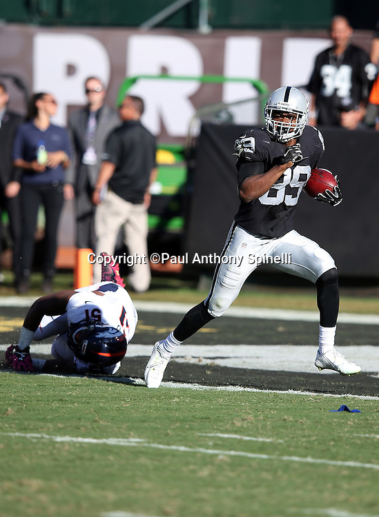 Oakland Raiders wide receiver Amari Cooper (89) runs away from Denver Broncos outside linebacker Todd Davis (51) as he returns a punt on the last play of the game during the 2015 NFL week 5 regular season football game against the Denver Broncos on Sunday, Oct. 11, 2015 in Oakland, Calif. The Broncos won the game 16-10. (©Paul Anthony Spinelli)