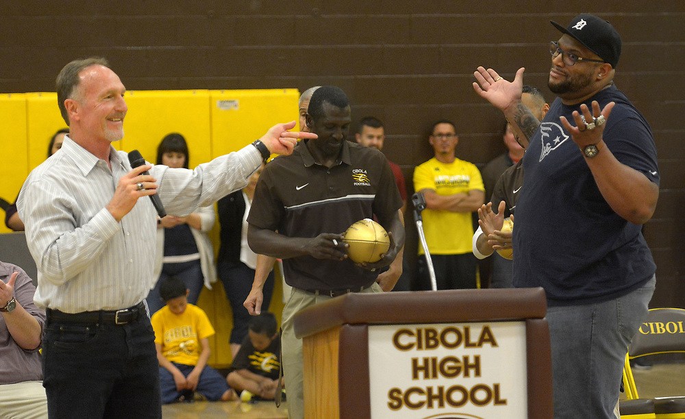 gbs050417b/SPORTS -- Former Cibola football coach Ben Shultz, left,  gets a reaction from former Cibola football player and current New England Patriots lineman Alan Branch, right,  during a program honoring him at Cibola on Wednesday, May 3, 2017. Cibola assistant coach Eric Jack, center, holds a NFL Superbowl ball autographed by Branch.(Greg Sorber/Albuquerque Journal)