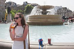 © licensed to London News Pictures. London, UK 17/07/2013. People enjoying the sunshine and hot weather in Trafalgar Square, London on Wednesday, 17 July 2013. Photo credit: Tolga Akmen/LNP