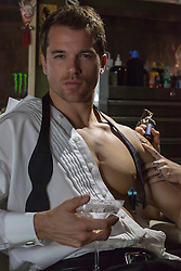 All American man getting a tattoo on his arm by a tattoo artist Sexy man in an open tuxedo shirt holding a martini while getting a tattoo