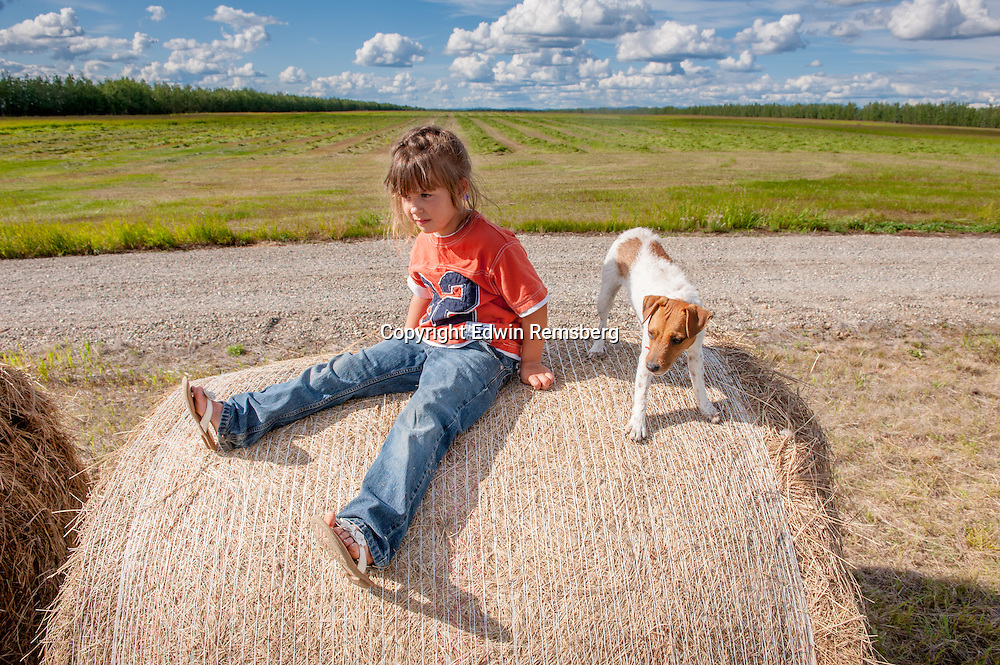 Portrait of a little girl sitting on a bale of hay with her dog