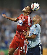 FC Dallas mid-fielder Tesho Akindele (13) heads the ball against Sporting KC defender Kevin Ellis (4) during the first half at Sporting Park.