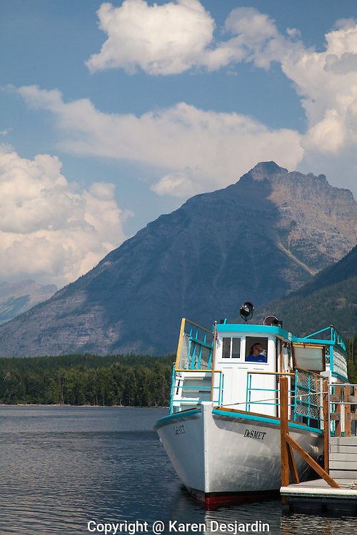 An historic wooden excursion boat waits at a dock on Lake McDonald in Glacier National Park, Montana.