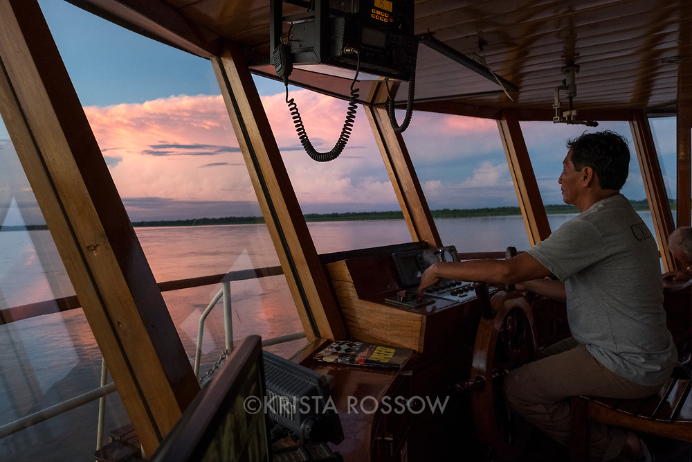 Crew members steer the Delfin II ship at sunset on the Marañon River. Pacaya Samiria National Reserve, Upper Amazon, Peru.