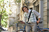 Man sitting on bicycle holding mobile phone