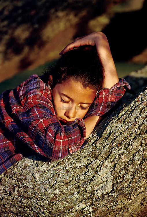 Young girl resting on the limb of a large tree.