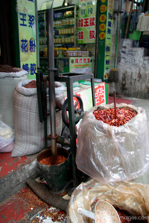 Asia, China, Chongqing. Grinding chili peppers into powder at local street market in the city of Chongqing.