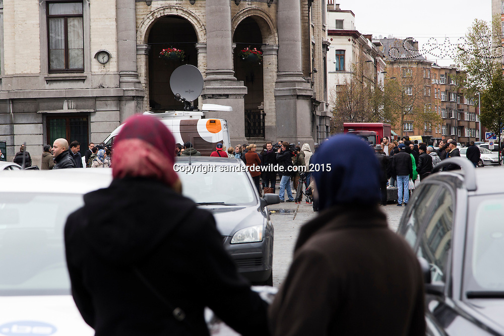 2015 november 16. Brussels, Belgium, Sint Jans Molenbeek.Two women with scarfs watch journalists interviewing Molenbeek officials after the minute of silence for the victims of the paris attacks.