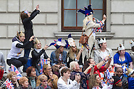 A crowd of onlookers in Parliament Square, London, cheering the arrival of guests and members of the British royal family prior to the wedding of Prince William to Catherine Middleton. The wedding was held at Westminster Abbey. Tens of thousands of people lined the streets to wish the couple well before and after the ceremony.