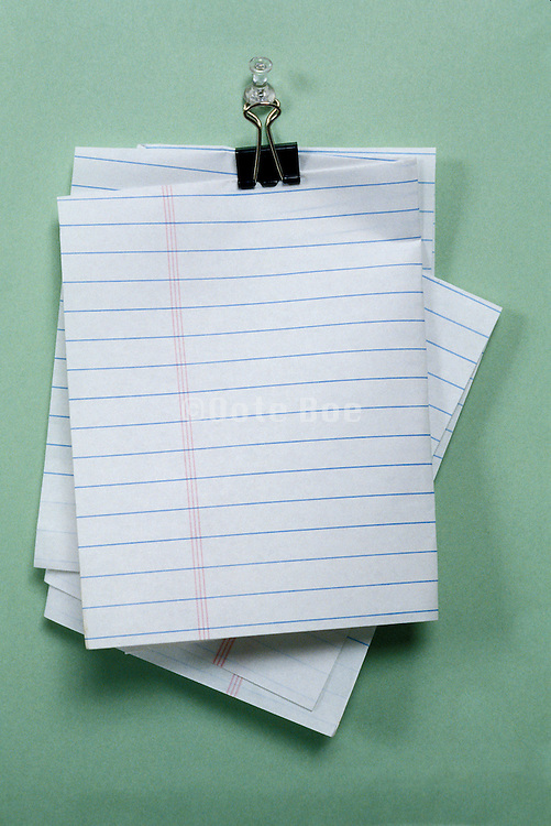 folded lined paper fastened by paper clip and hung on push pin