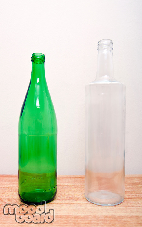 one green glass bottle and one clear glass bottle