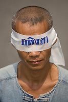 "BANGKOK, THAILAND  -  March 14: A man wears a blind fold that says ""Peaceful"" as he joins tens of tousands of demonstrators seeking the resignation of Prime Minister Thaksin Shinawatra marched to government house on March 14, 2006 in Bangkok, Thailand. Marching several kilometers from the Grand Palace to Government House the protesters surrounded Thaksin's office chanting ""Thaksin Get Out"", as the Prime Minister threatened a state of emergency if the demonstration turned violent.  (Photo by David Paul Morris)"