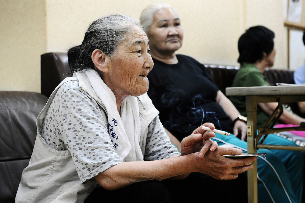 Three elderly women, each of whom previously has been homeless and jobless, watch TV in the communal room of a former hotel that has been converted into accommodation for homeless community who have passed mandatory retirement age in the Kamagasaki district of Osaka, Japan. Elderly homeless aged 65 and over are eligible for special governmental benefits that allows them to stay in relatively more comfortable accommodation than their under-65 counterparts, which, in the central Osaka district of Kamagasaki, costs around 42,000 yen (360 euro) a month and provides lodgers with communal bath and TV facilities and a 7 sq.-meter room -- barely big enough to fit a single bed and refrigerator. .Photographer: Robert Gilhooly