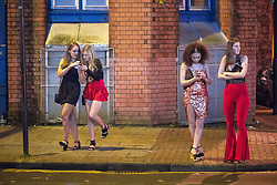 "© Licensed to London News Pictures . 16/12/2017. Manchester, UK. Two pairs of women wait on the pavement at Deansgate Locks . Revellers out in Manchester City Centre overnight during "" Mad Friday "" , named for historically being one of the busiest nights of the year for the emergency services in the UK . Photo credit: Joel Goodman/LNP"