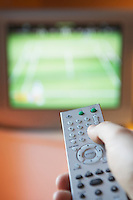 Man changing TV channel with remote control close-up on hand