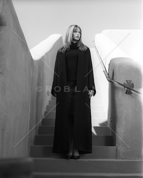 woman in a long coat standing on a staircase in New Mexico