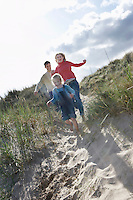 Parents and daughter (5-6) running through sand dunes