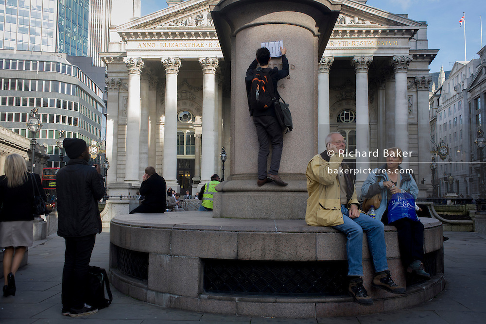 Sticking a sign to a City of London statue in Cornhill EC4.