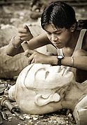 A man sculpting a wooden statue of Buddha, Mahamuni pagoda, near Mandalay, Burma (Myanmar)