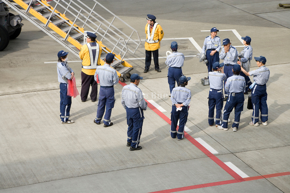 cleaning crew waiting for airplane to arrive at Narita International airport Tokyo Japan