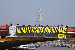 © Licensed to London News Pictures. 12/07/2018. London, UK. Activists from Amnesty International unfurl a giant protest banner on Vauxhall Bridge in London as President of the United States Donald Trump arrives in the United Kingdom. Photo credit: Rob Pinney/LNP