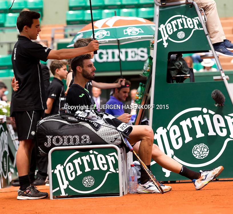 Marcel Granollers (ESP) sitzt auf der Bank w&auml;hrend der Spielpause,im Hintergrund unscharf Roger Federer,Court Suzanne Lenglen,<br /> <br /> <br /> Tennis - French Open 2015 - Grand Slam ITF / ATP / WTA -  Roland Garros - Paris -  - France  - 27 May 2015.