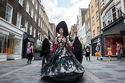 London, UK. 2 July, 2019. Climate change activists from Extinction Rebellion Art and Culture pass along South Molton Street during a silent procession to visit the offices of five major oil companies - ENI, CNPC, Saudi Aramco, Repsol and BP - in order to declare them as crime scenes.