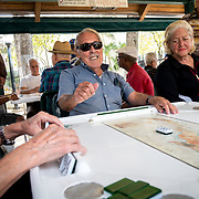 MIAMI, FLORIDA, APRIL 22, 2017<br /> Pedro Raya, 86 in blue shirt, laughs as he plays dominoes  in Miami's Little Havana neighborhood's Maximo Gomez Domino Park. Many Miami Cubans voted for Donald Trump in the general elections. Trump will soon complete his first 100 days as United States President.<br /> (Photo by Angel Valentin/Freelance)