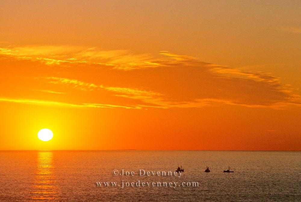 Three fishing boats off Monhegan Island at sunrise