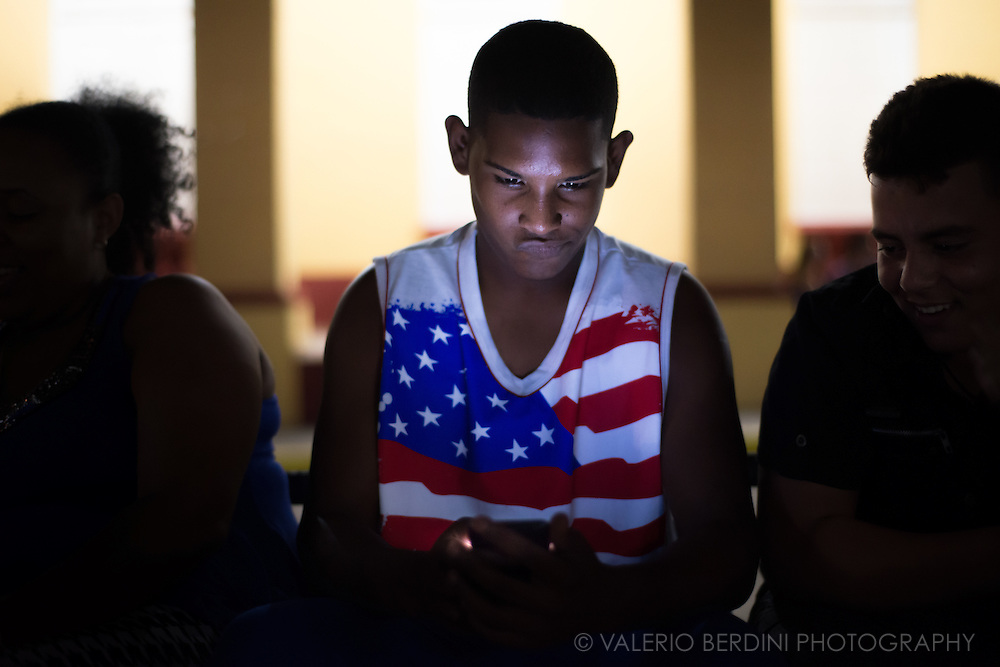 A boy in a USA flag tank top, lit up by the screen of his smartphone sits in front of the porticate of Plaza Carillo in Trinidad de Cuba, on the night of 26 December 2015.  Great fans of American sports, Baseball and Basketball mainly, Cubans can now get live information about their favourite teams online. This boy was aware of the photographer, but he continued using the device. This photo was not staged.