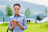 Young attractive businesswoman using smartphone outdoors