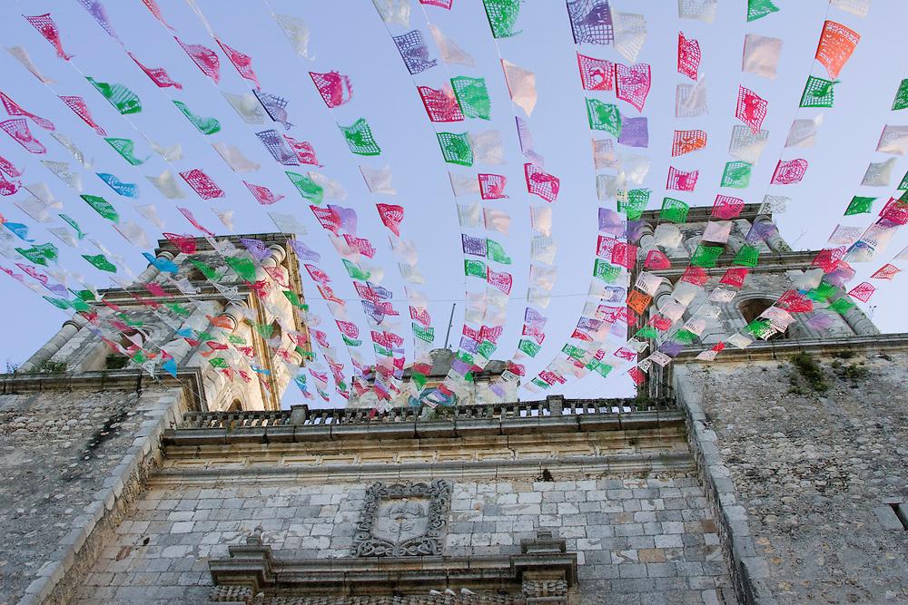 Mexico, Yucatan, Valladolid, La Parraquia de San Servacio church on Plaza Mayor, with colorful flags fluttering in wind