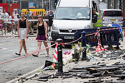 © Licensed to London News Pictures . FILE PICTURE DATED 15/07/2013 . Oldham Street , Manchester , UK . Flowers , tributes and a uniform left at the scene , in front of Paul's Hair World . The scene on Oldham Street following a fire at Paul 's Hair World on 13th July which claimed the life of fireman Stephen Hunt . Photo credit : Joel Goodman/LNP