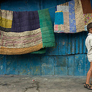 Blankets being aired outside a house in Dharavi's pastic recycling area.