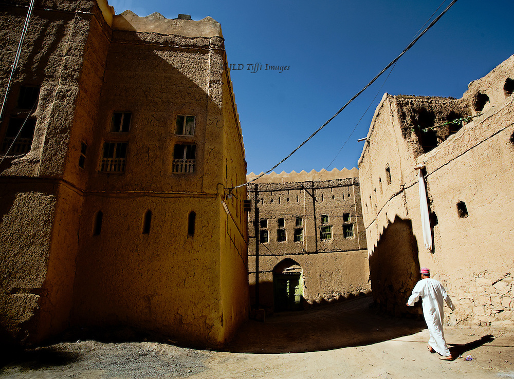 Oman, mud brick village of Al Hamra, largely abandoned.  Though some structures still endure, and show some basic maintenance, little restoration seems to be attempted. Here a man wearing white dishdasha and red cap strides, arms swinging, down a street under a heavy electrical wire. Bright midday sun casts heavy shadows.