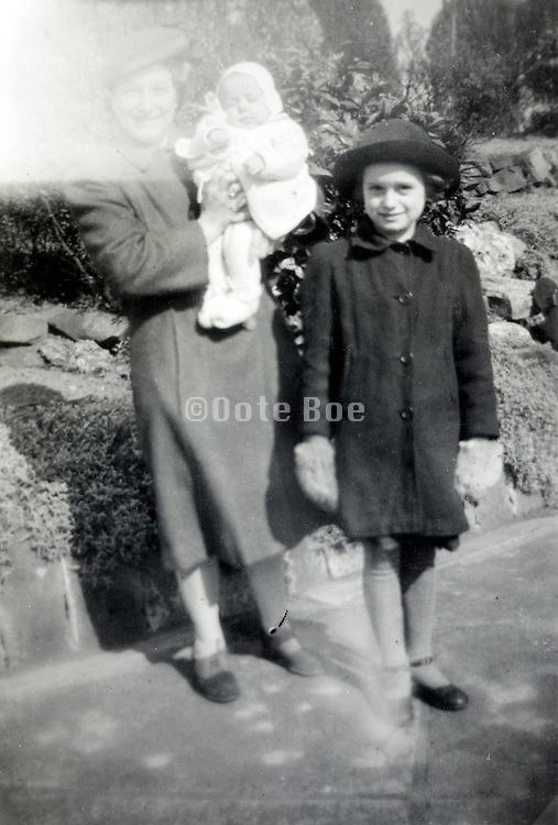 print from negative with a light flair of a happy mother holding her baby and a young child