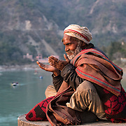 A baba meditates on the banks of the Ganges River at Rishikesh, Uttarakhand, India.