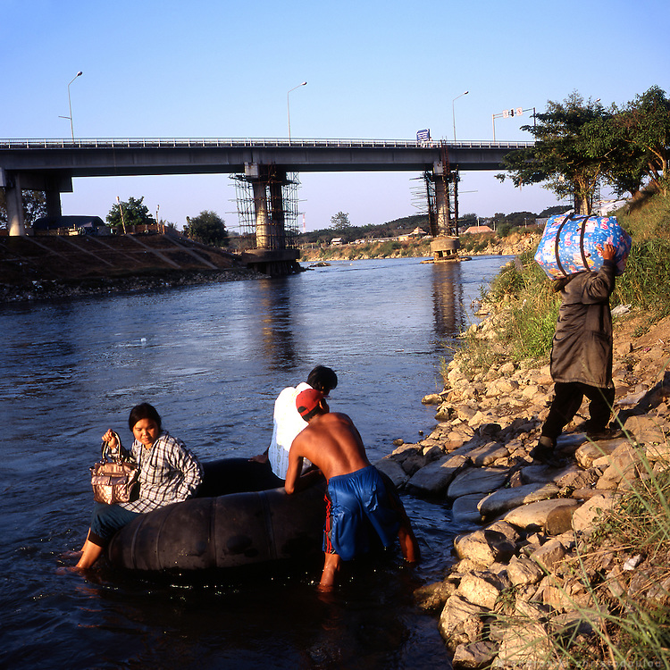Illegal crossing of people and goods between Burma and Thailand on a inflated track-tire tube that is pushed back and forth through the river on a regular basis, a few hundrends of meters away from the bridge that is the official border crossing.
