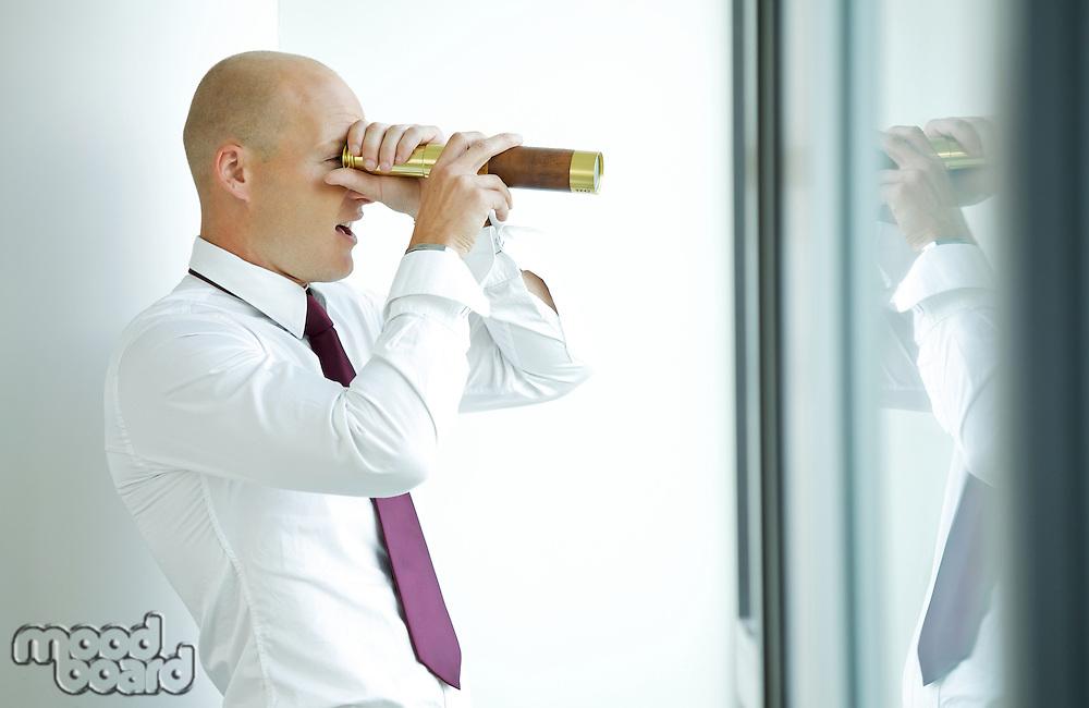 caucasian businessman spying using telescope thru office window