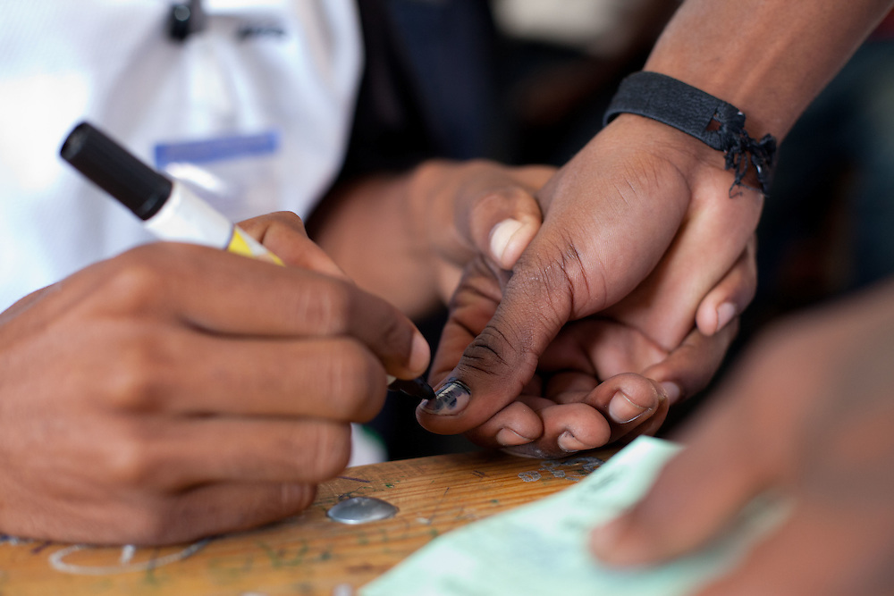 Voters get their thumbs marked with indelible ink after voting.