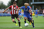 AFC Wimbledon striker Lyle Taylor (33) dribbling and taking on Brentford defender Harlee Dean (6) during the EFL Cup match between AFC Wimbledon and Brentford at the Cherry Red Records Stadium, Kingston, England on 8 August 2017. Photo by Matthew Redman.