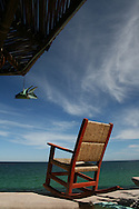 Rocking chair looking the blue waters of Sea of Cortez. At the corner you can see Mexican palapa and a fish decoration. The photo reveals very relaxing, leasure feeling. Perfect to enjoy your summer vacations, your second-home retreat or your beach residence.