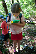 8 year old girl observes mosquito larvae during a nature walk at summer camp.