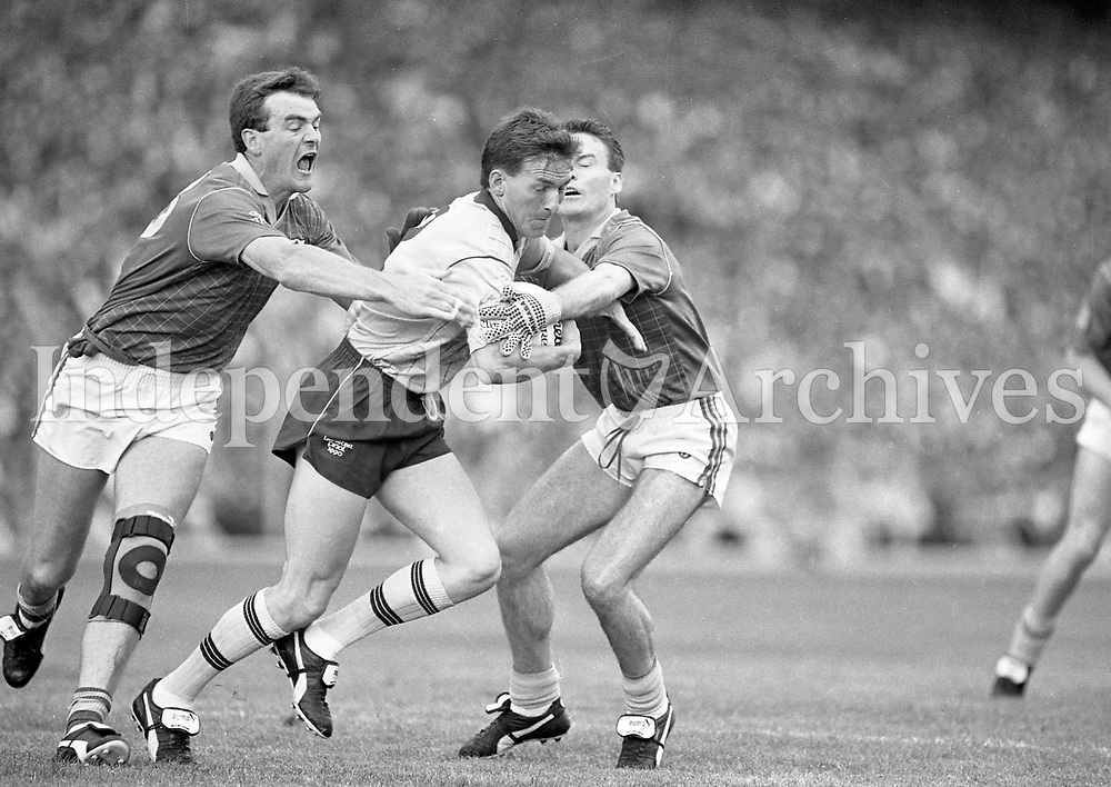 790-630<br /> Leinster Football Final at Croke Park, Dublin v Meath, 29th July 1990:<br /> Mick Deegan (Dublin) tries to break away from Meath's forwards Colm O'Rourke (left) and Bernard Flynn.<br /> Meath 1-14 Dublin 0-14<br /> Pic: Dara Mac Donaill, 29/7/90<br /> (Part of the Independent Newspapers Ireland/NLI Collection)