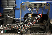 The rear of a cab, its chassis and hydraulic control hoses of an HGV lorry parked at a supermarket distribution depot